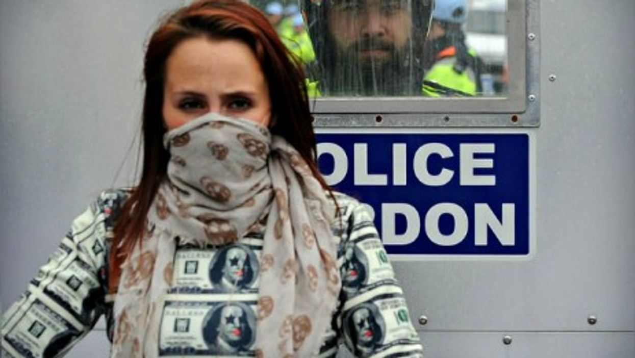 A policeman looks at a masked protester Thursday during the first day of the 2014 NATO Summit held in Newport, Wales.