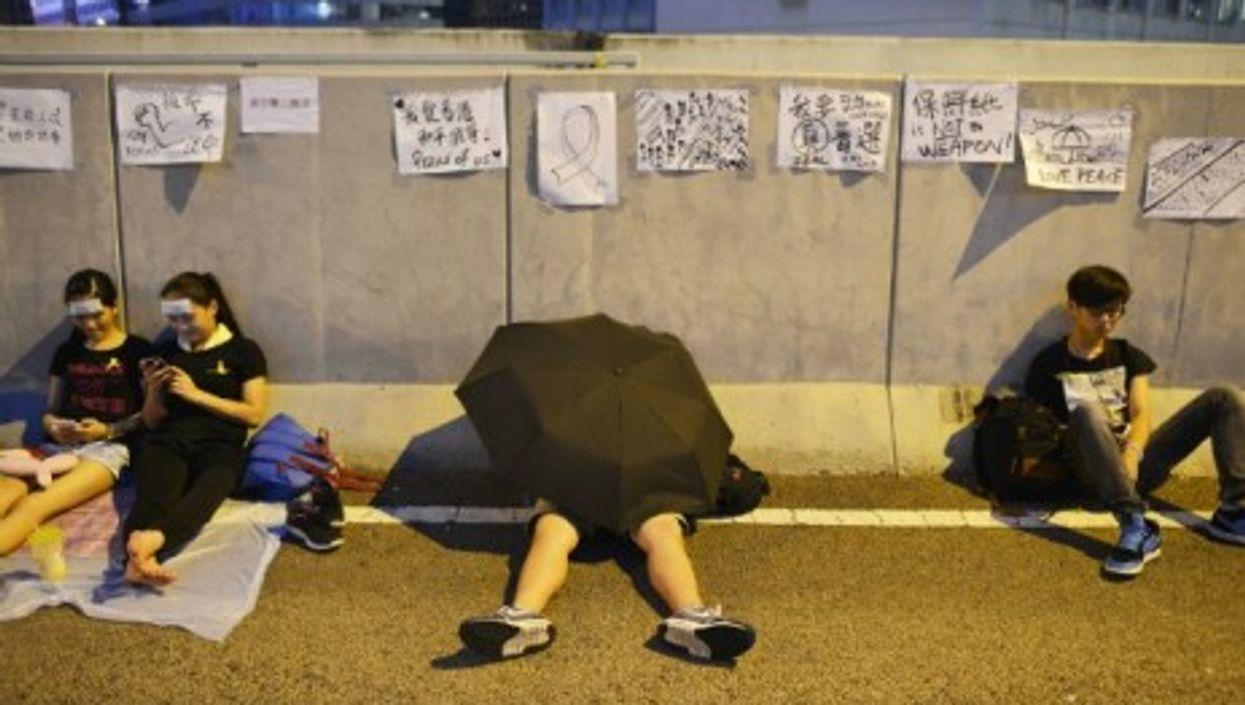 A pro-democracy protestor rests under an umbrella.