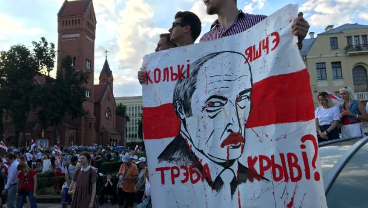 A protester holds up a sign that reads 'How much more blood will it take?' in Independence Square in Minsk, Belarus.