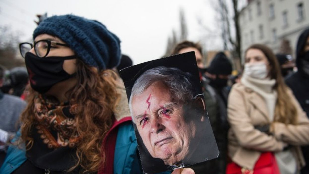 A protester in Warsaw holds a placard with an image of Jaroslaw Kaczynski