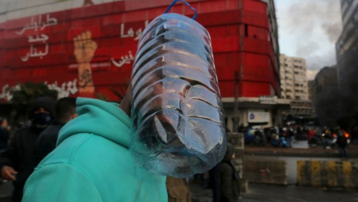 A protester uses a plastic water container as a mask to protect him from tear gas during a demonstration in Tripoli, Lebanon, against the national lockdown and the worsening economic conditions.