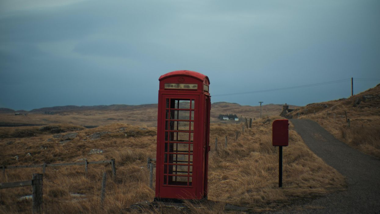 A red phone booth alongside the road