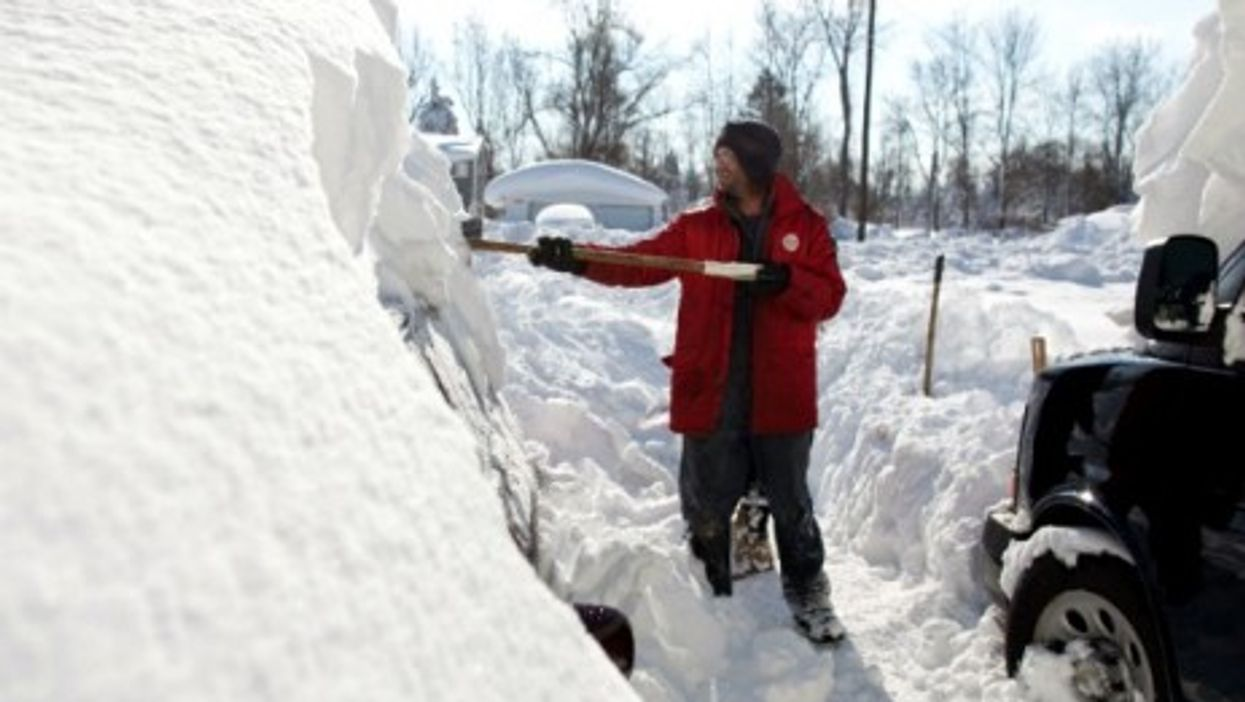 A resident of Alden, New York, shovels snow from atop his car.