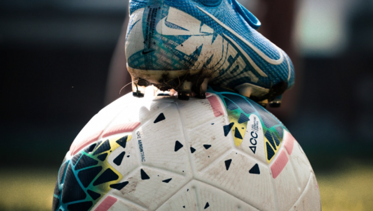 A soccer player places their foot on a soccer ball
