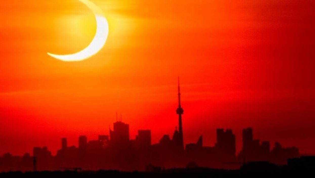 A solar eclipse shines over the skyline of Toronto, Canada