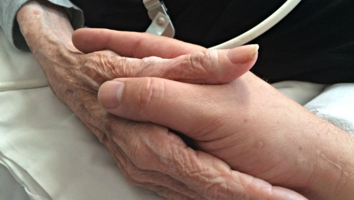 A son holding his mother's hand in a palliative care facility in Oakland, United States on June 26, 2015