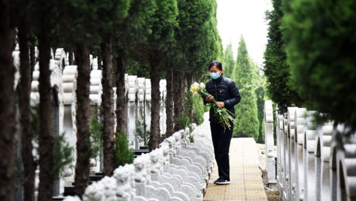 A staff member distributes flowers at a cemetery in Jinan, in eastern China.