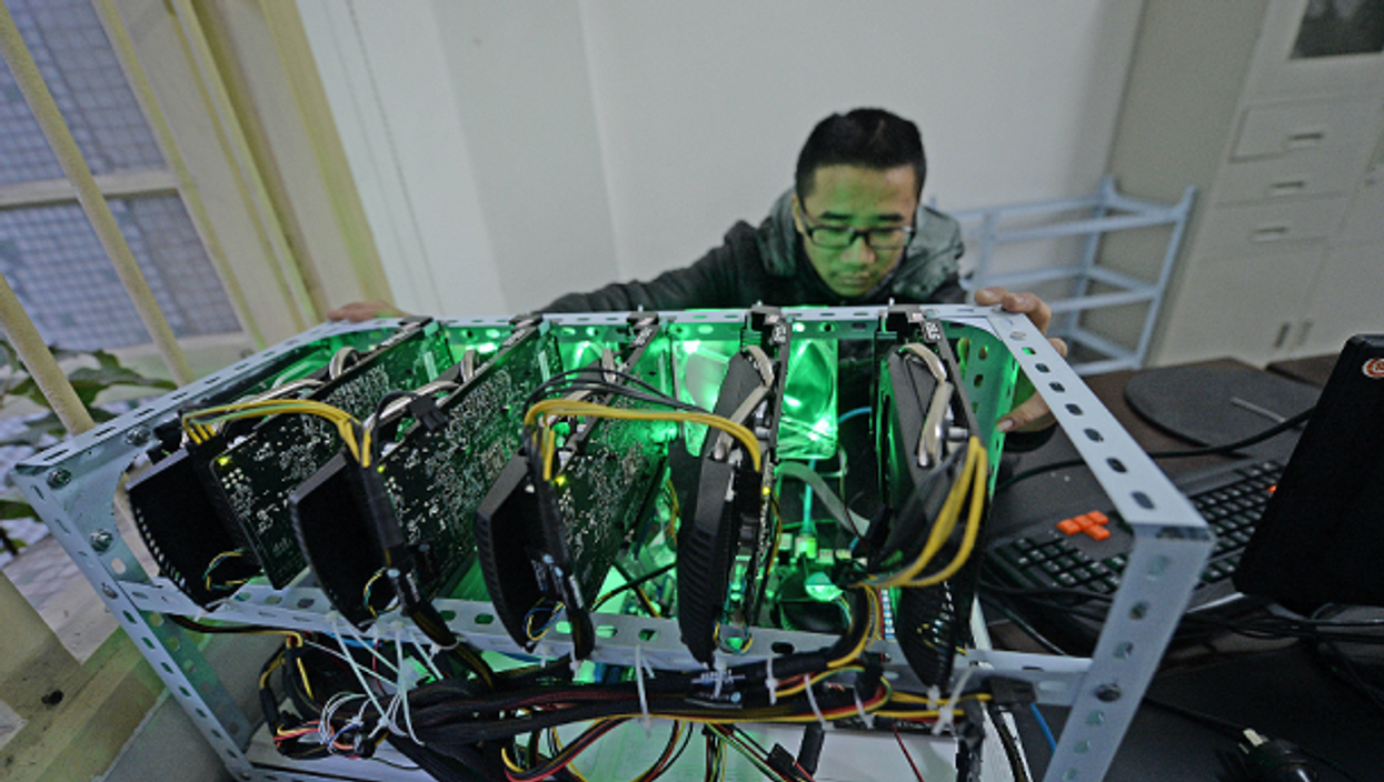 A staff monitors a 'bitcoin miner', a powerful computer with five mining cards