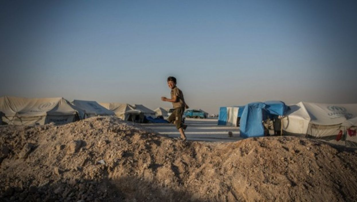 A Syrian boy running through a refugee camp in Ain Issa, Northern Syria