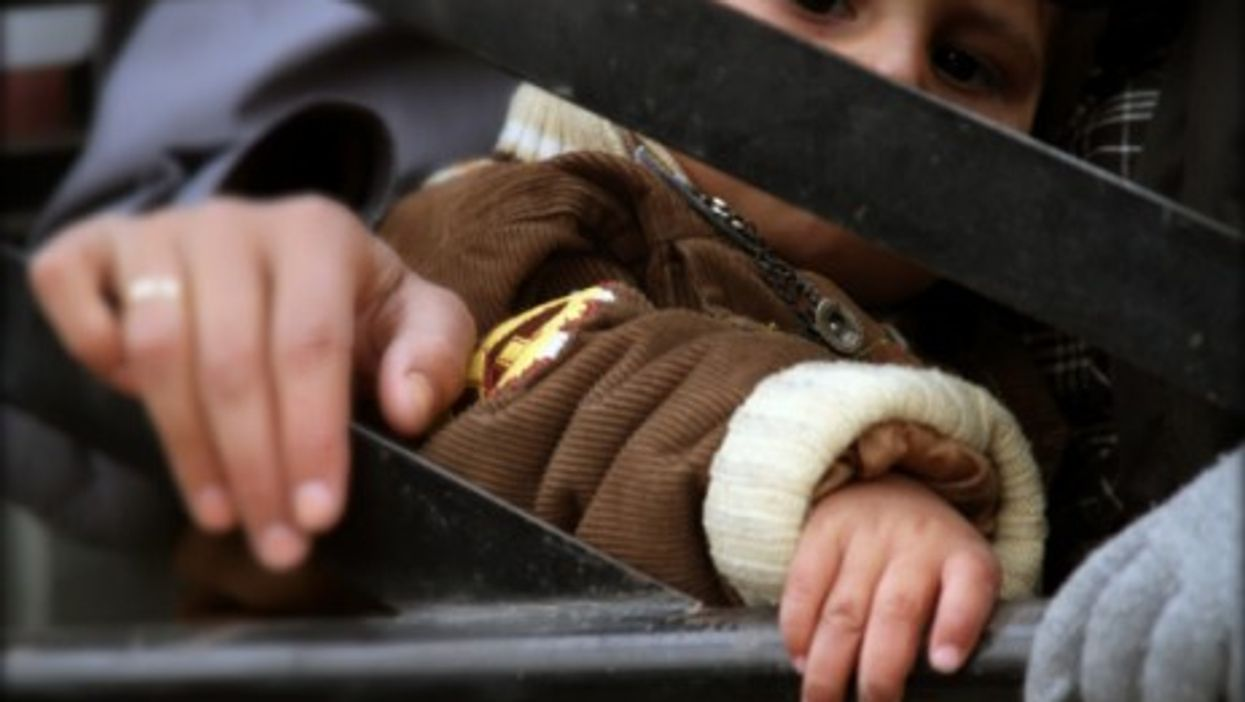 A Syrian child comes back into al-Moadamiya, a district on the outskirts of Damascus that has been besieged by the government troops for months, in Syria, March 2, 2014.