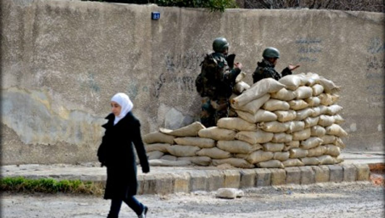 A Syrian girl walks past Syrian army soldiers in Harasta, near Damascus