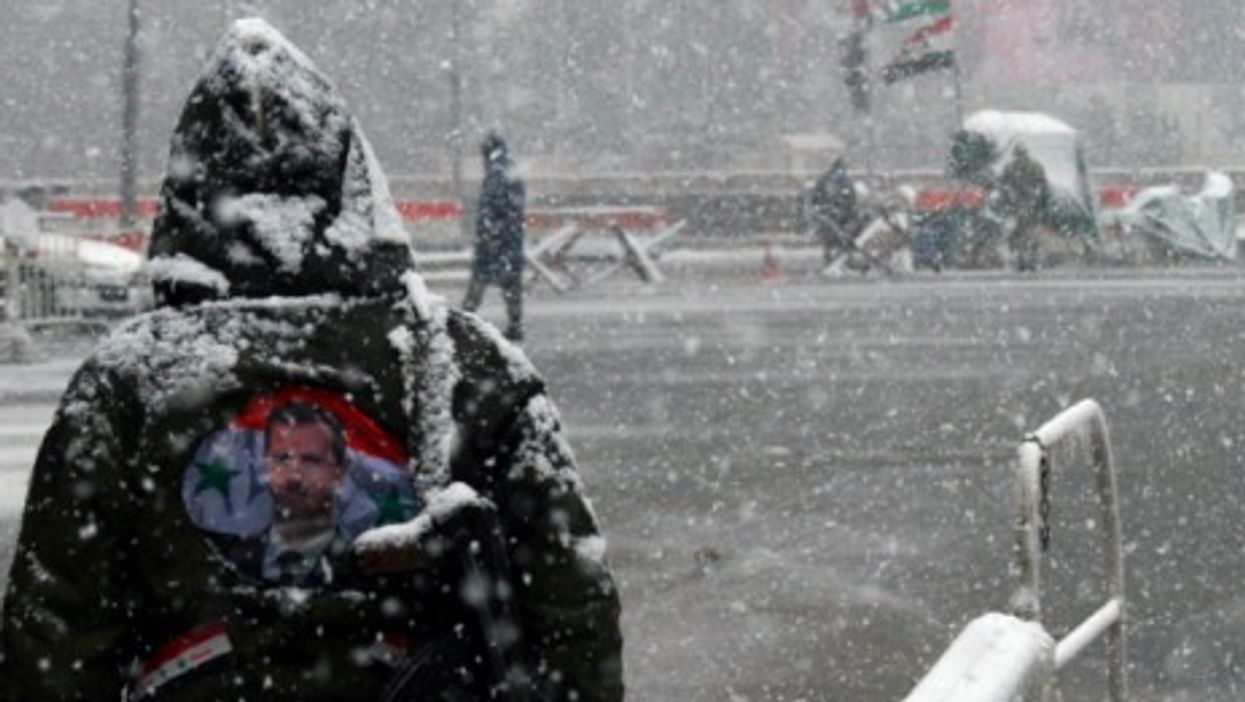A Syrian government soldier stands in the snow in central Damascus.