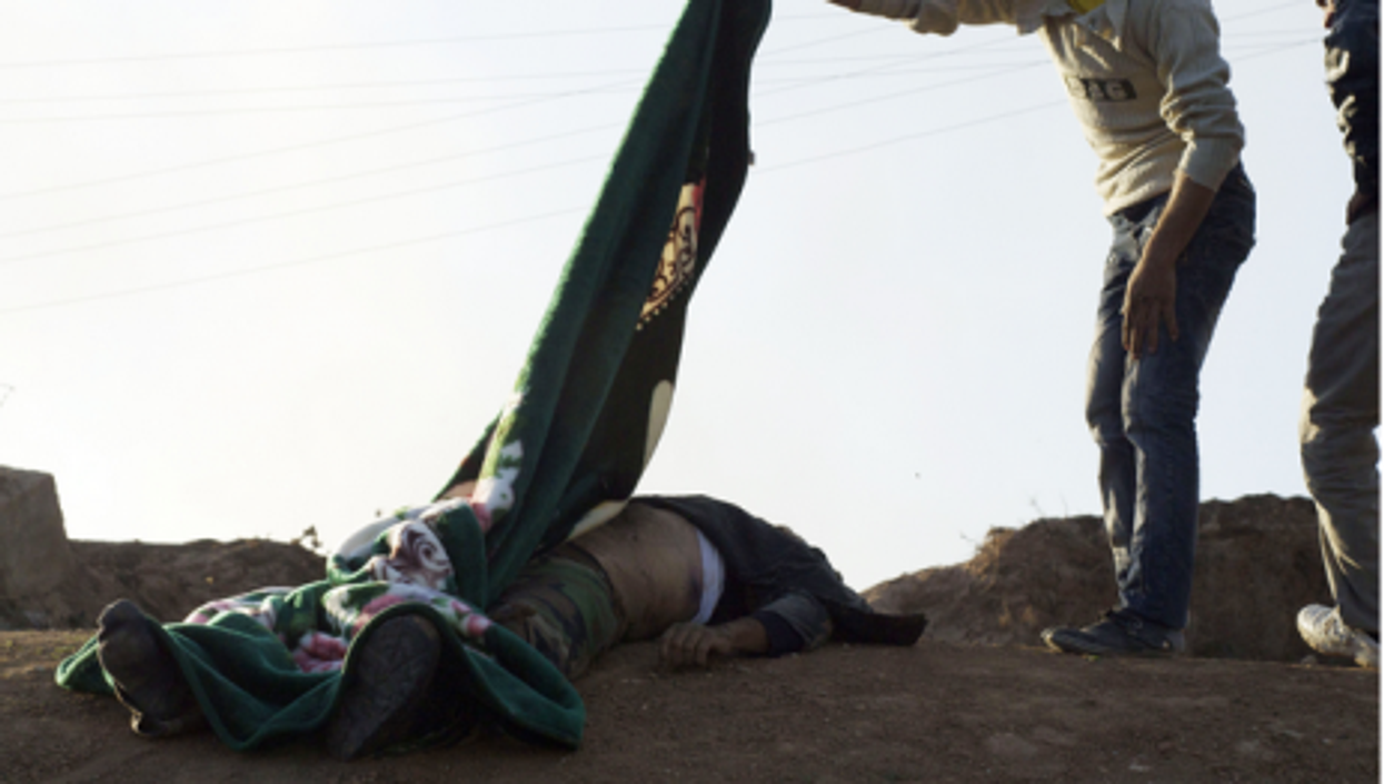 A Syrian man covers a dead Syrian army soldier with a blanket after a battle last year near Ras al Ayn, Syria