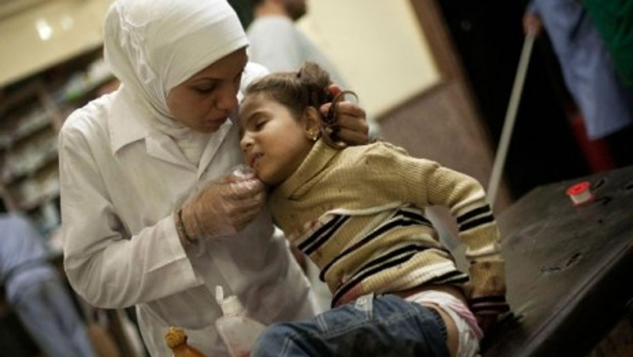A Syrian nurse caring for a little girl after her house was bombed by Assad militias, in November 2012.