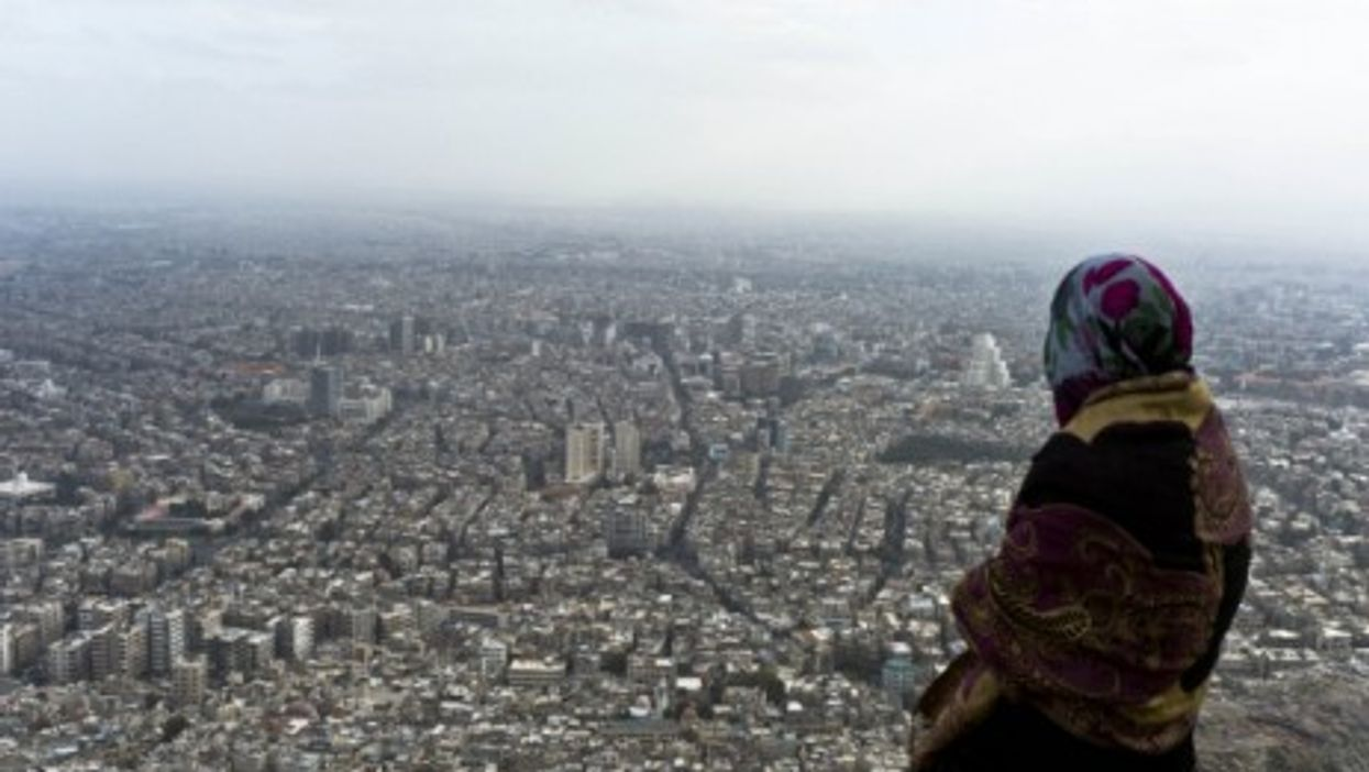 A Syrian woman looks over Damascus