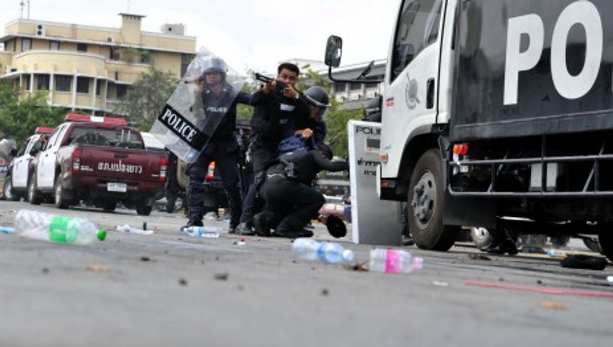 A Thai riot police officer fires on anti-government protesters in Bangkok today.