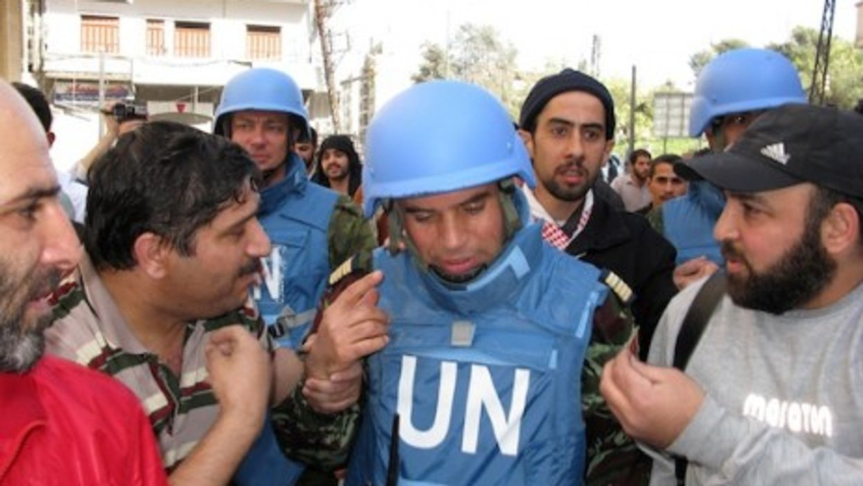 A UN Military officer surrounded by citizens of Homs (UN)