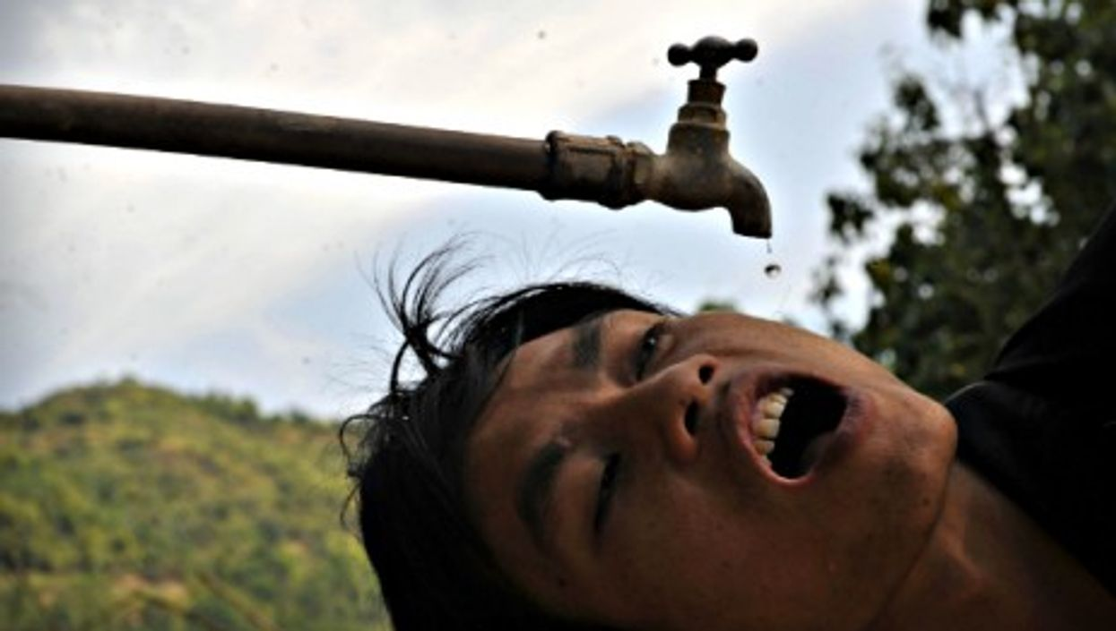A villager drinks drips of water in Zhongbang Village, southern China