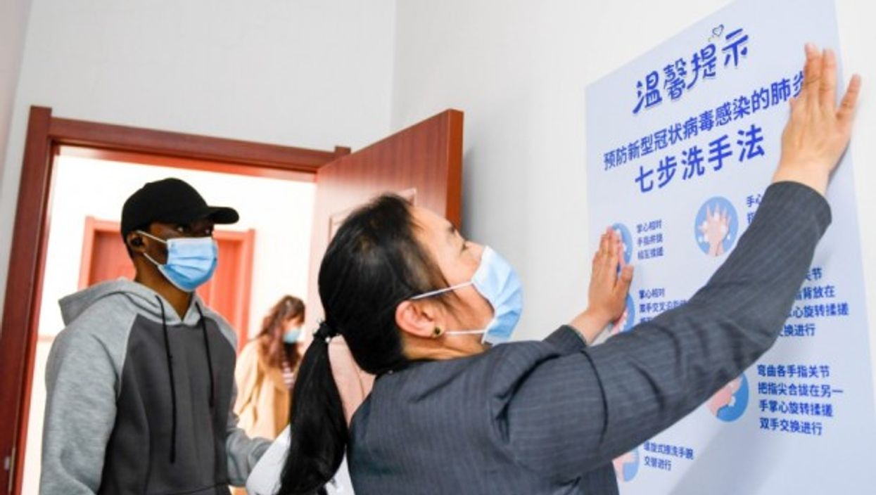 A visiting medical student watches a teacher to post anti-epidemic poster in Changchun University.