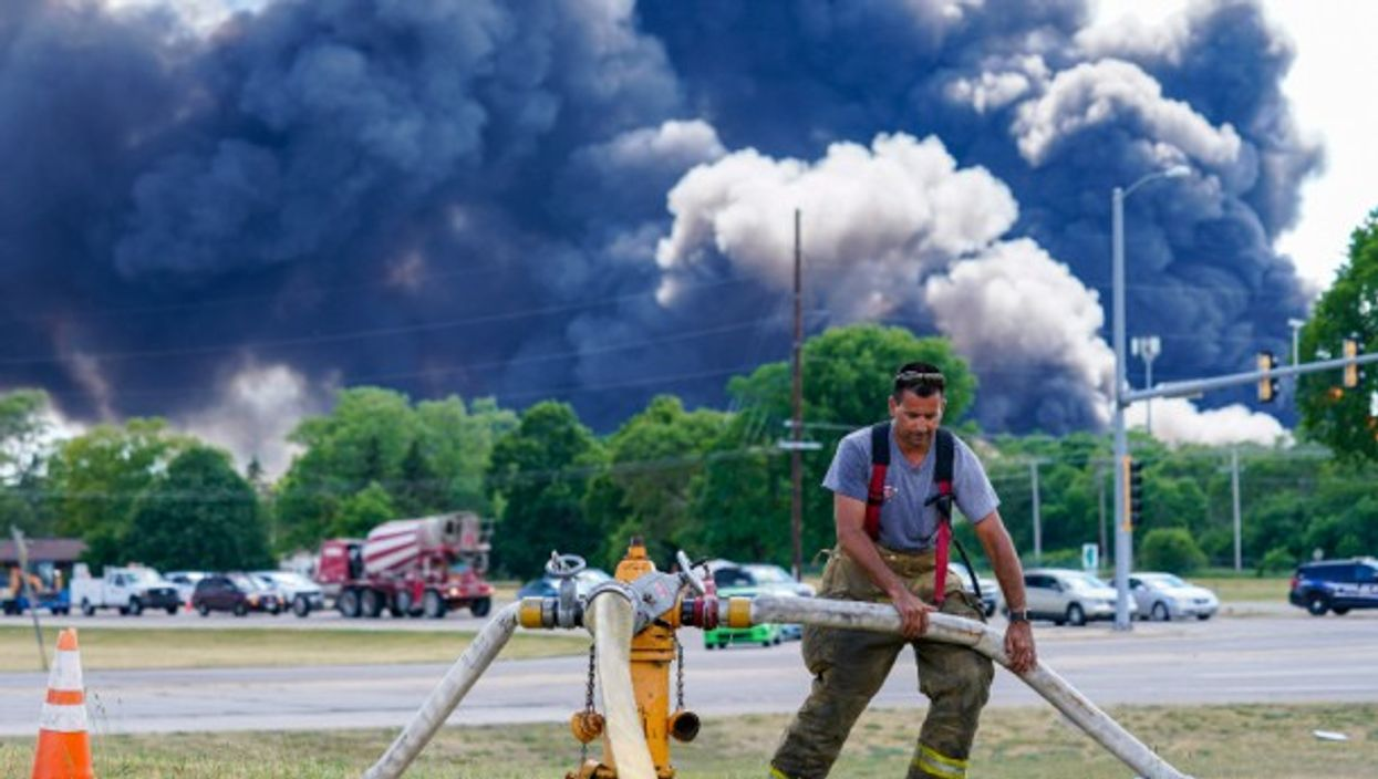 A volunteer firefighter helps put out the massive fire that broke out yesterday at a chemical plant in Rockton, Illinois. Residents within a one-mile radius of the site have been evacuated, as authorities warn that the blaze could last for days.