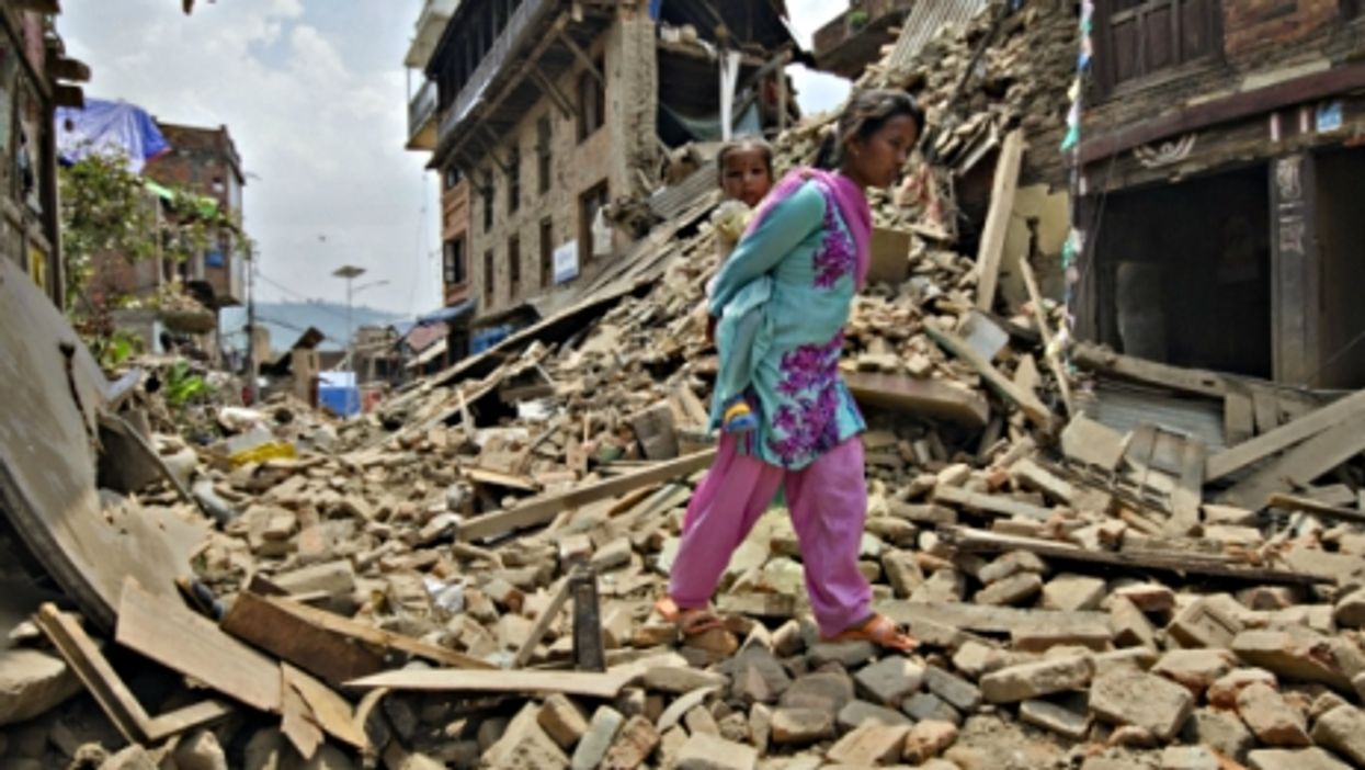 A woman carrying her baby through the debris of Kathmandu on May 16