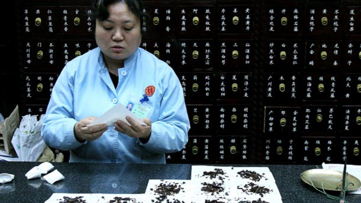 A woman in Beijing packaging medicine
