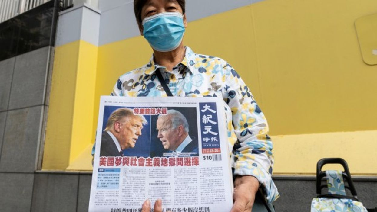 A woman in Hong Kong distributes copies of the Epoch Times