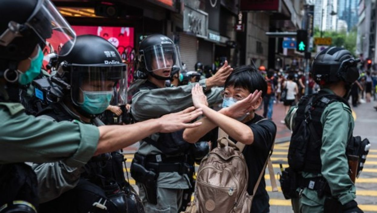A woman in Hong Kong makes a gesture in front of riot police during a protest.