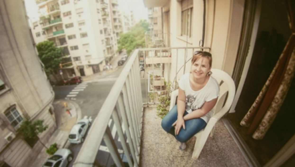 A woman on her tiny balcony in Buenos Aires