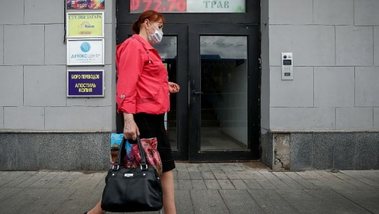 A woman passes a currency exchange office in Moscow, Russia