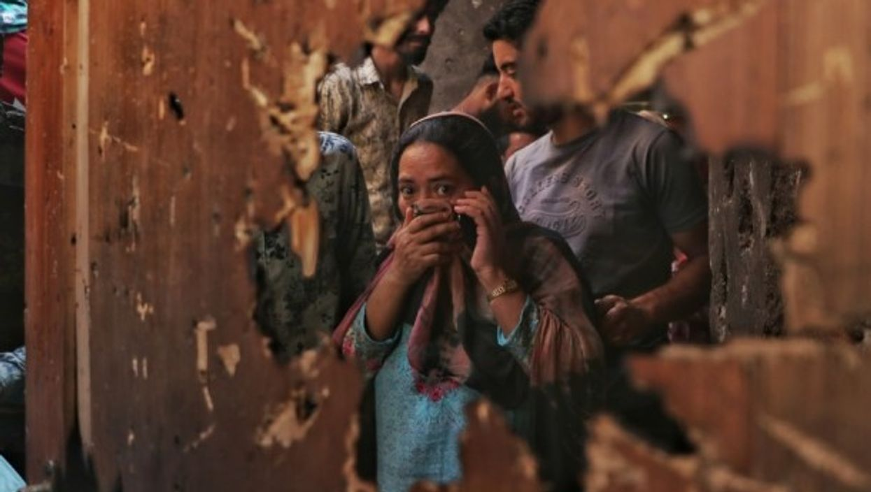 A woman reacts to the damage left from a gunfight between militants and police in the Kashmiri city of Srinagar