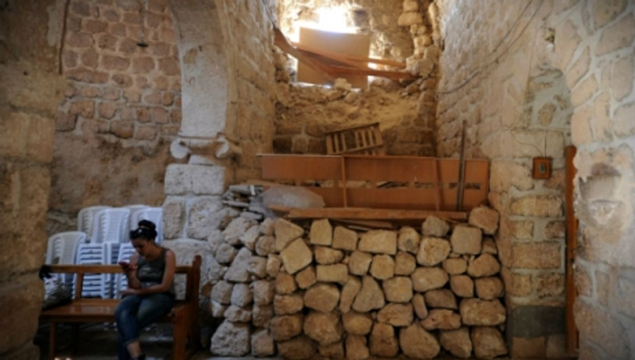 A woman sits in a church in the historic Christian town of Maaloula, north of Damascus