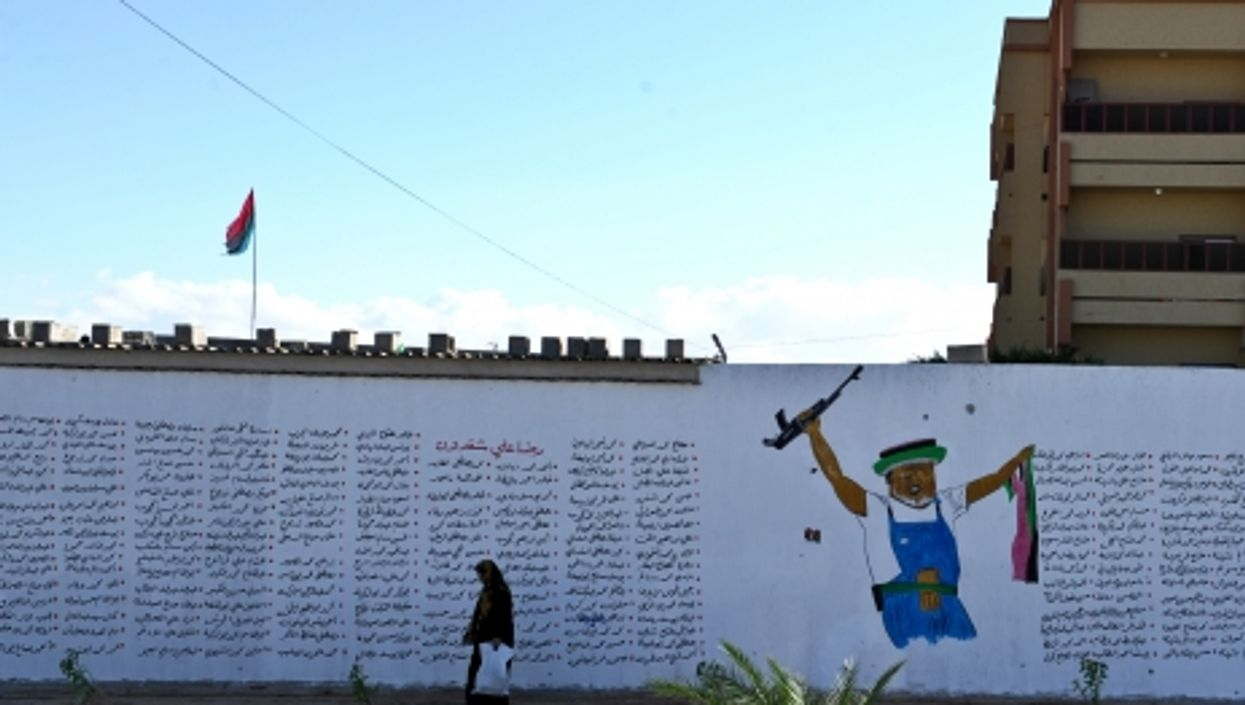 A woman walks past a wall full of names of people who died during the Libyan Civil War, in Misrata.