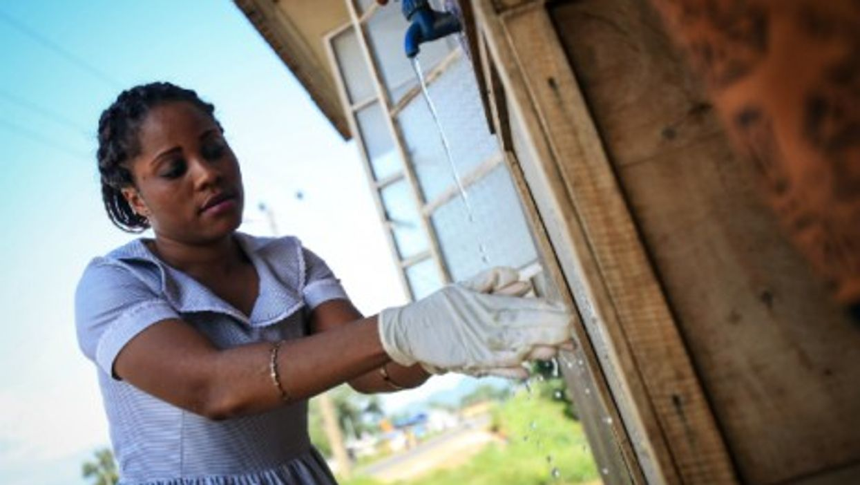 A woman washes her hands outside a community health center in Ebola-affected Freetown.