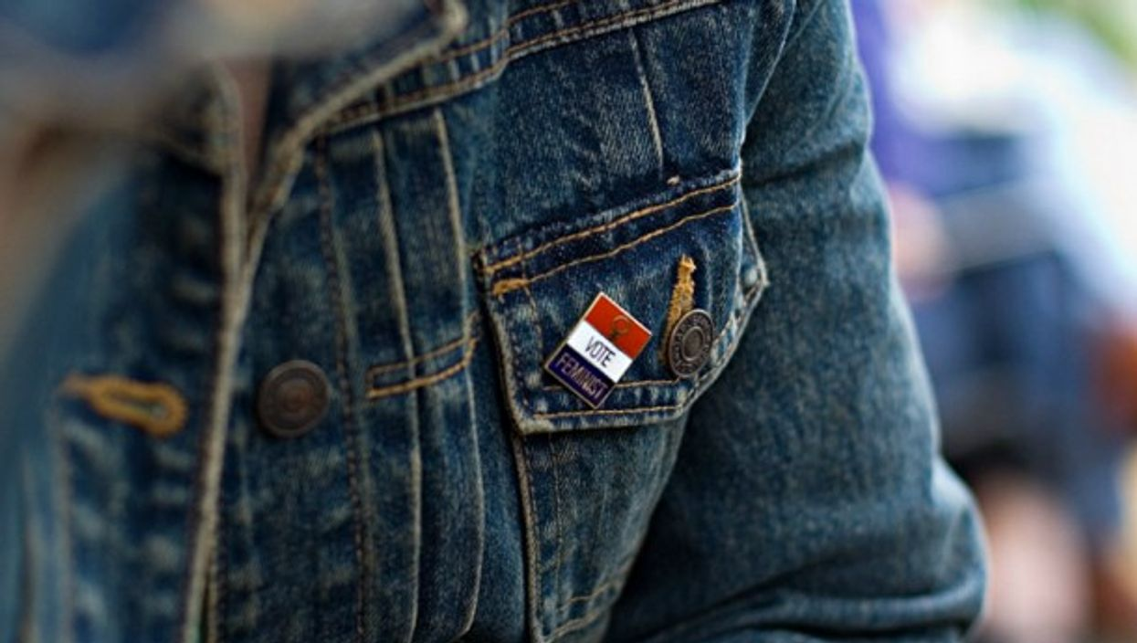 A woman wears a feminist pin on her jean jacket.