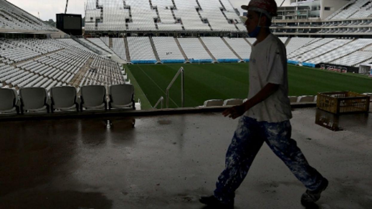 A worker walks inside the Sao Paulo Arena