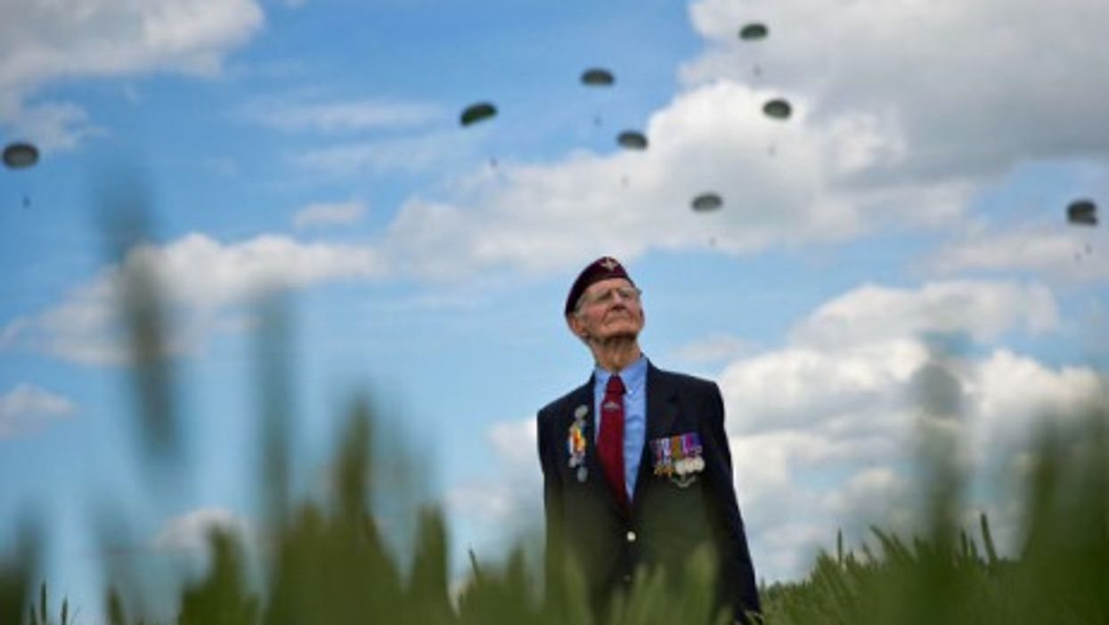 A WWII veteran watches a landing by paratroopers in Ranville, Normandy