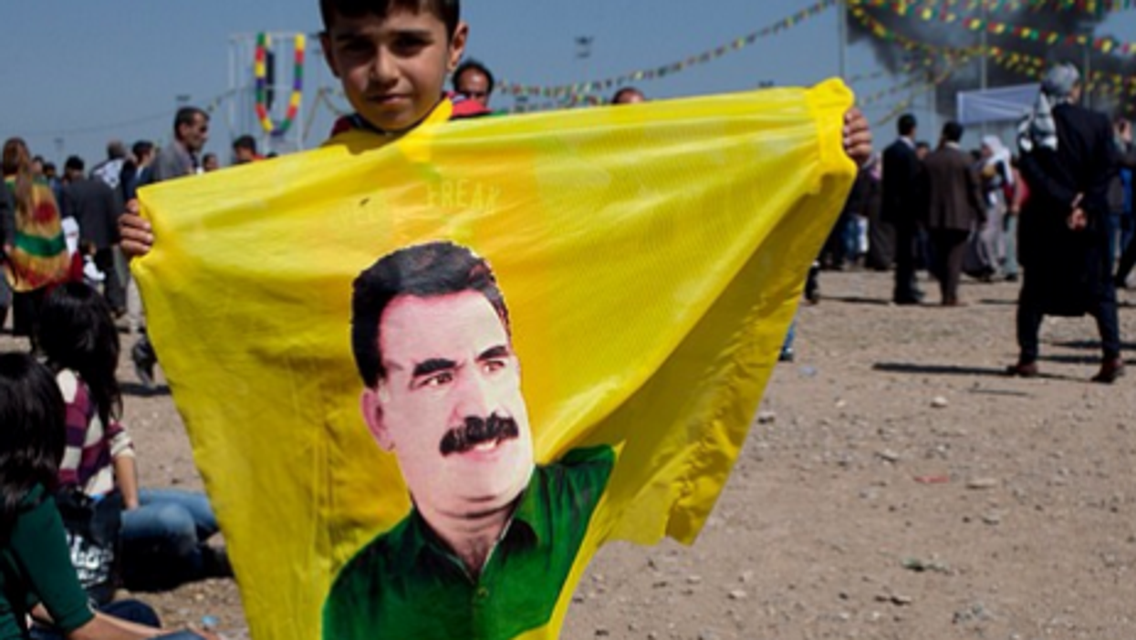 A young boy holds a flag with Ocalan's face at the Newroz celebrations