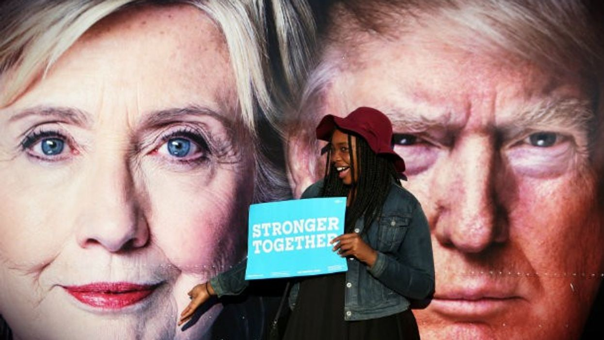 A young Clinton supporter poses in front of posters of the two candidates before Monday's debate.