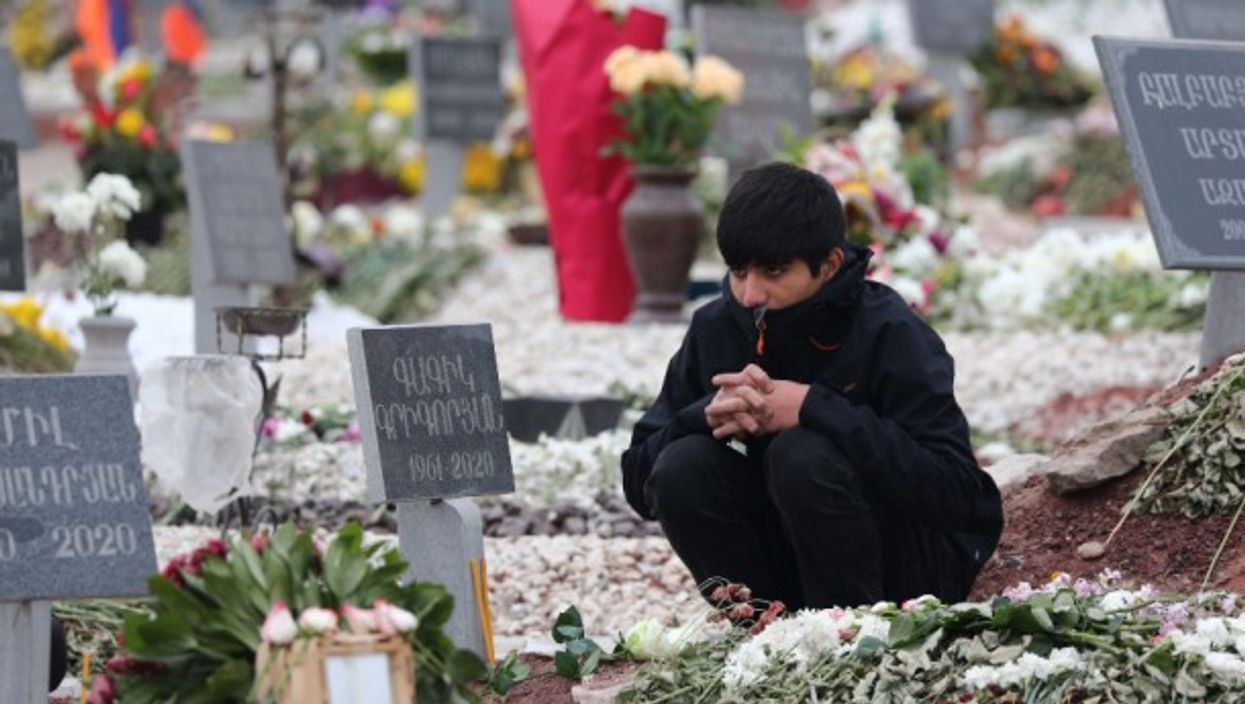 A young man visits the grave of an Armenian serviceman killed during the Nagorno-Karabakh conflict in Yerevan