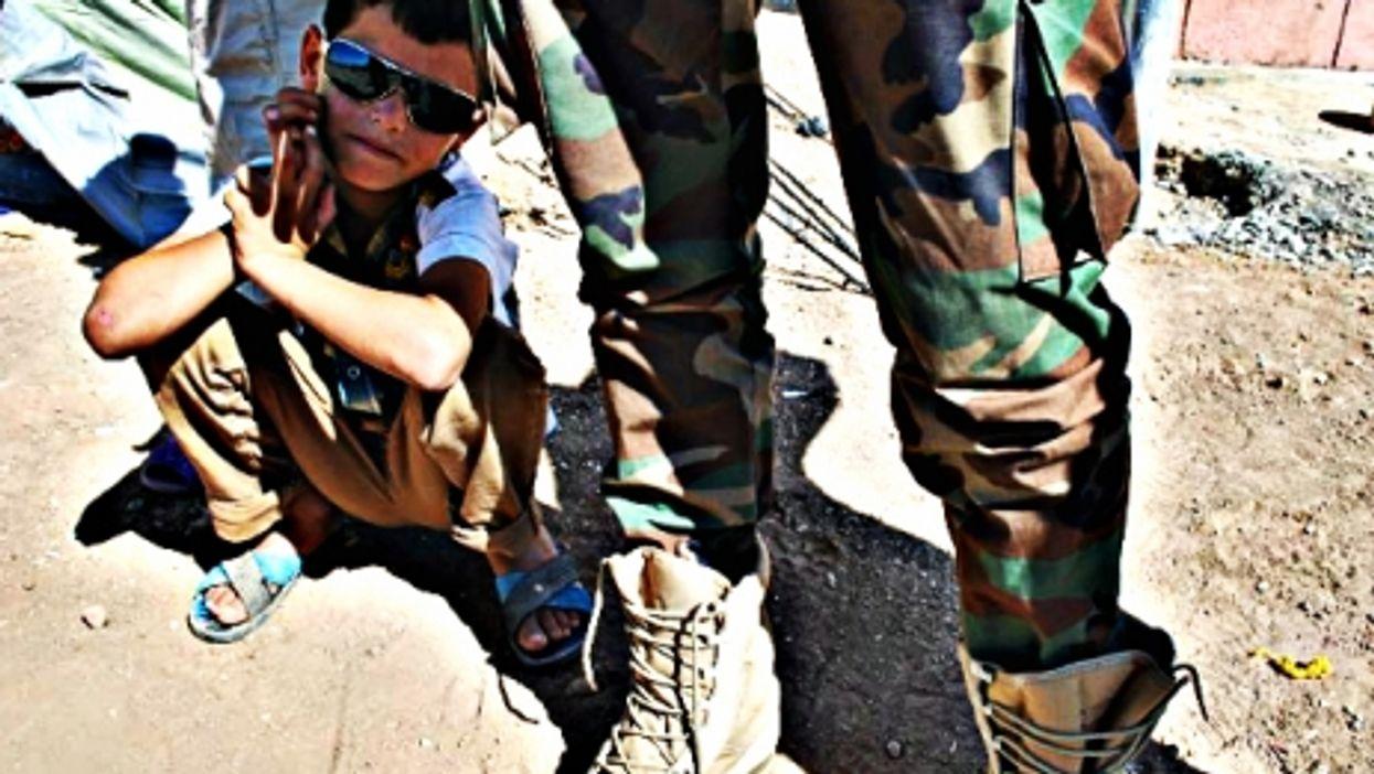 A young Syrian Kurd near a Syrian Kurdish soldier