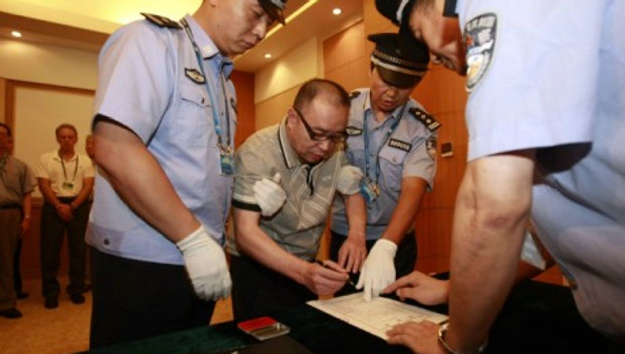 Alleged smuggling kingpin Lai Changxing signs a warrant issued for his arrest as he arrives at the Beijing Capital International Airport on July 23, 2011.