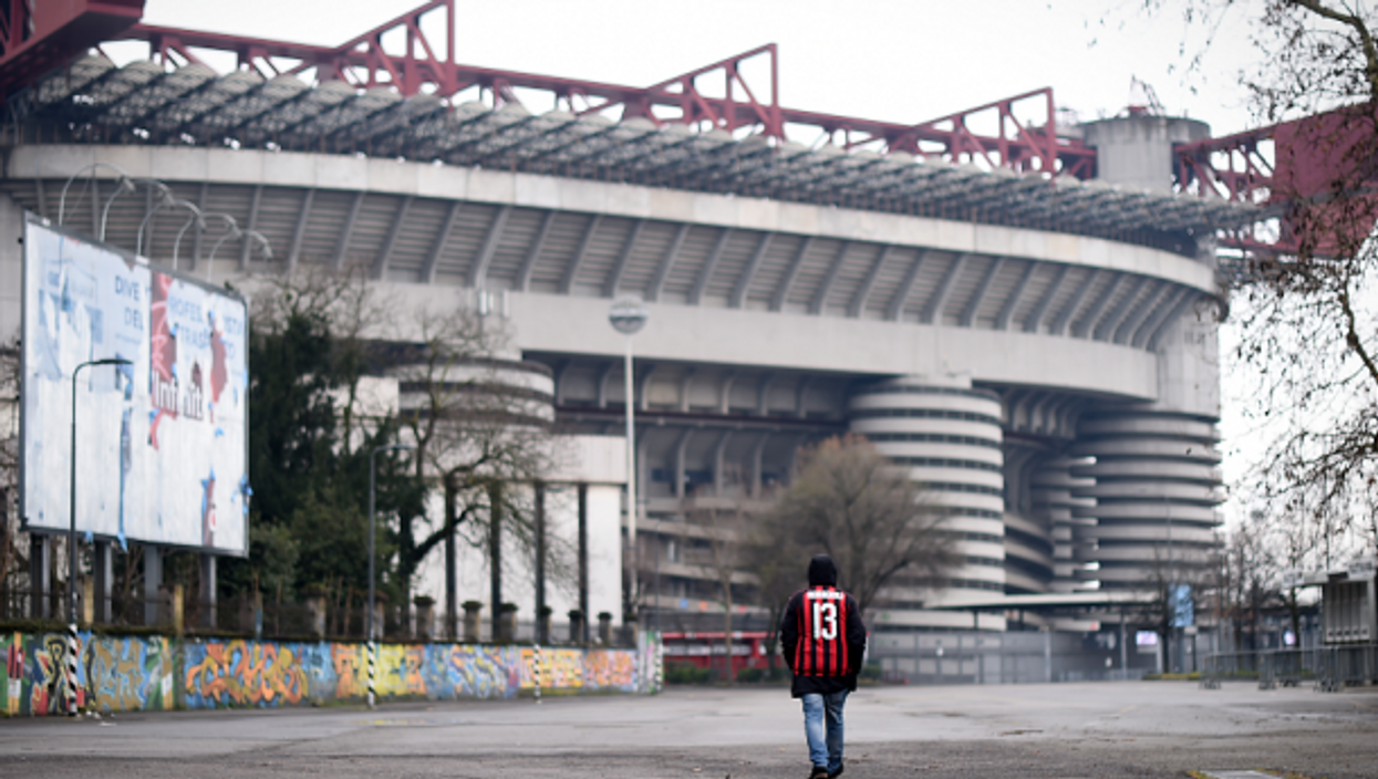 An AC Milan fan outside the iconic San Siro stadium in March 2020