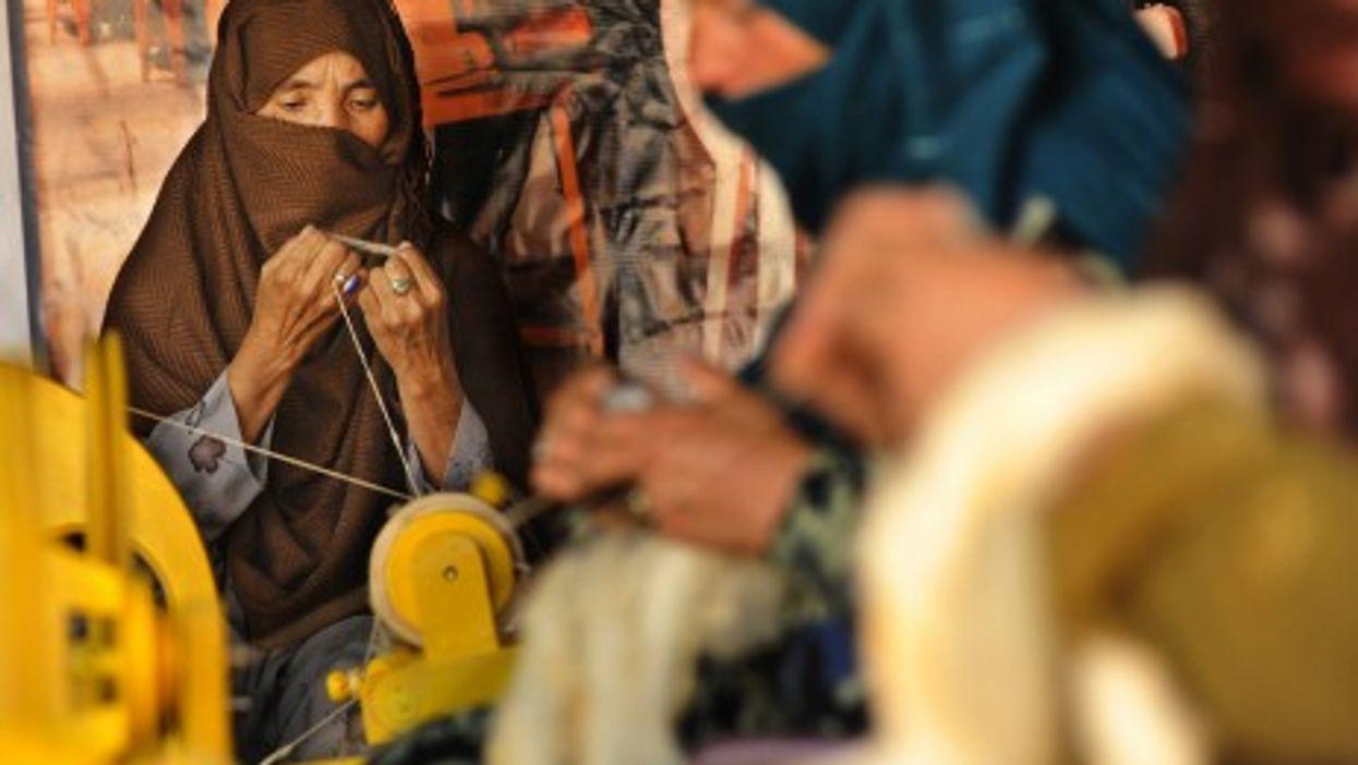 An Afghan woman spins wool into yarn in Kabul (isafmedia)