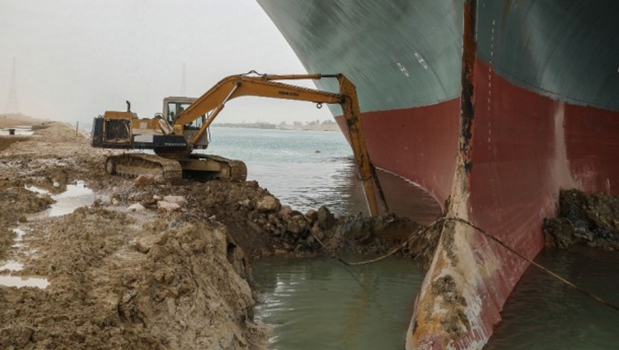 An excavator attempts to free the front end of the Ever Given, the container ship which is currently blocking the Suez Canal