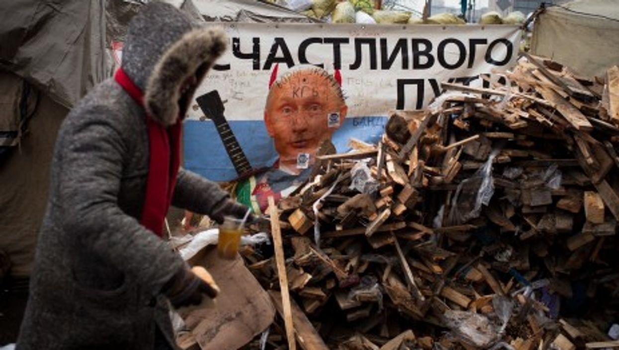 An image of President Putin peeks from behind barricades in Independence Square, Kiev.