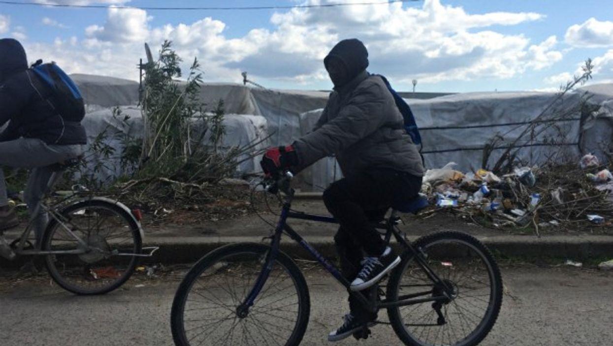 An immigrant rides a bike along a shantytown in San Ferdinando, Italy