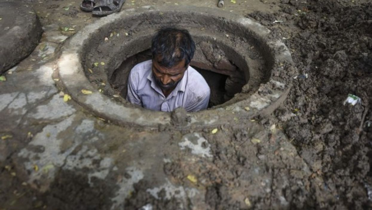 An Indian manual scavenger cleans a manhole in New Delhi in August 2018