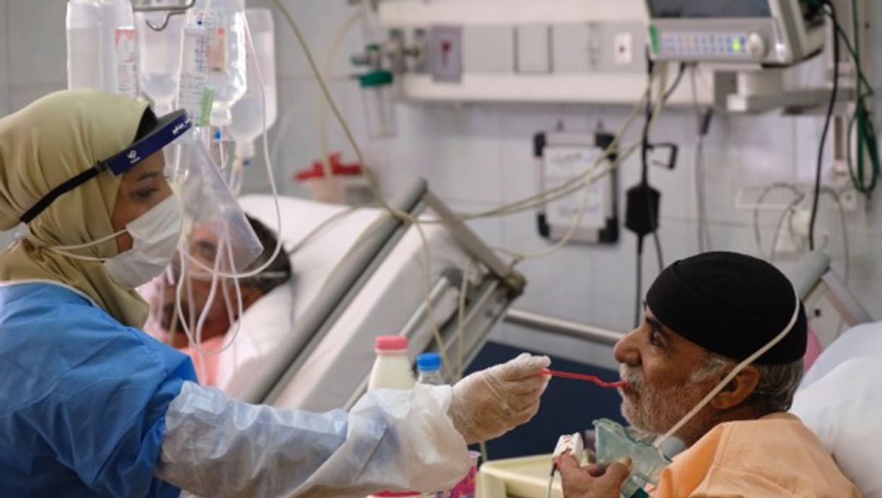 An Iranian medical personnel feeding a patient in a hospital in southern Tehran