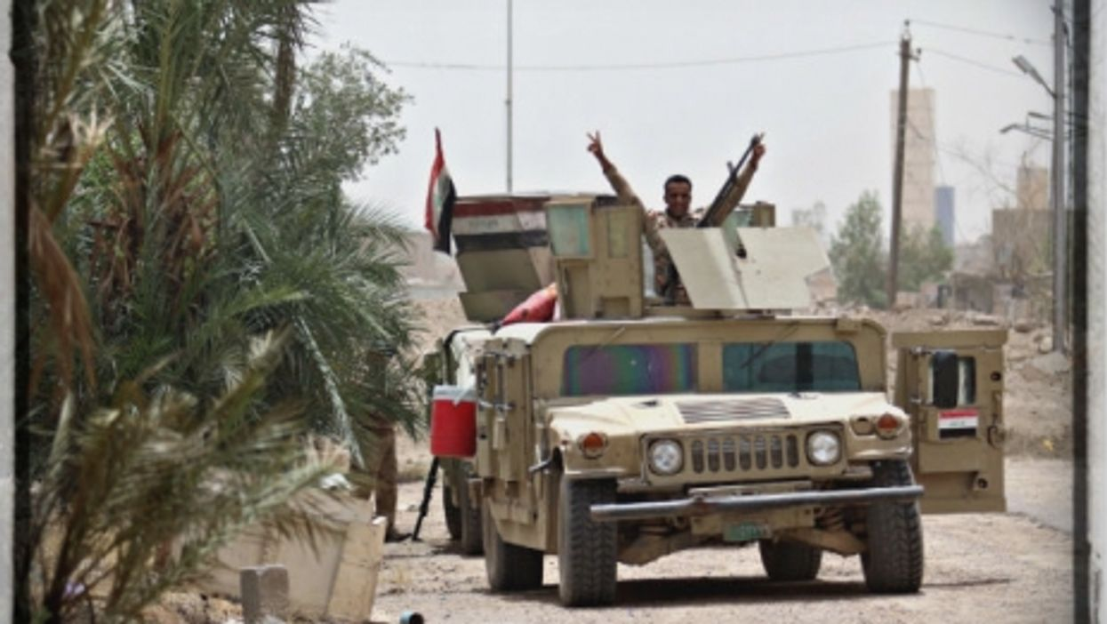 An Iraqi government soldier claims victory in Fallujah on June 20